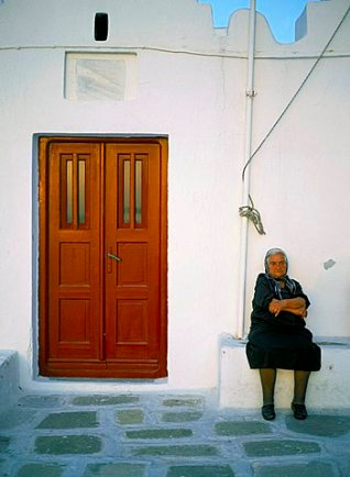 Old lady sitting by church, Mykonos (Mikonos), Cyclades Islands, Greek Islands, Greece, Europe